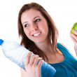 Young woman with bottle of water and apple — Stock Photo #21282565