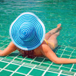 Royalty-Free Stock Photo: Woman in hat relaxing at swimming pool