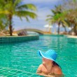 Woman in hat relaxing at swimming pool — Stock Photo #21907981