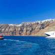 Speedboat at high volcanic cliff of Santorini island — Stock Photo #22999990