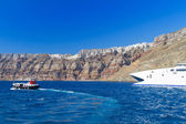 Speedboat at high volcanic cliff of Santorini island — Stock Photo