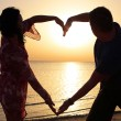 Couple making romantic heart shape at sunrise — Stock Photo