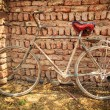 Dusty old bike at brick wall — Stock Photo