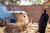 Arabská žena pečení chleba v beduínské vesnici — Stock fotografie