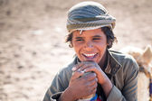 Pojke arbetar med kameler i beduin byn på öknen — Stockfoto