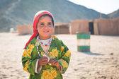 与骆驼在沙漠上的贝都因人村工作的女孩 — 图库照片