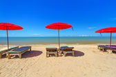 Red parasol with deckchair on tropical beach — Stock Photo