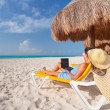 Woman with laptop relaxing on the deckchair — Stock Photo