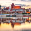 Stock Photo: Torun old town reflected in Vistulriver at sunset