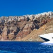 Stock Photo: Speedboat at high volcanic cliff of Santorini island