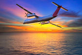 Aircraft flying at sunset — Stock Photo