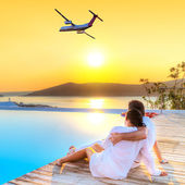 Couple in hug watching airplane at sunset — Stock Photo