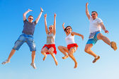 Group of friends jumping with happiness — Stock Photo