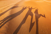 Shadow silhouettes of four people in the desert — Stok fotoğraf