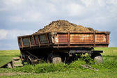 Tow tractor with horse manure standing on pasture — Stock Photo