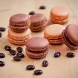 Chocolate and caramel macaroons on wooden table — Stock Photo