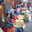 Balinese woman in market sell flower petals for everyday offering — Stock Photo