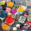 Stock Photo: Balinese woman in market sell flower petals and fruits for everyday offering