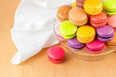 Traditional french colorful macarons in a glass cake stand on wooden table — Stock Photo