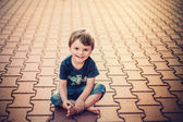 Smiling little boy sitting on the ground — Stock Photo