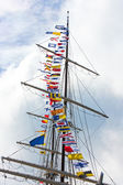 International flags on sailing ship's mast — Stock Photo