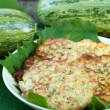 Pancakes with fresh zucchini on grape leaves — Stock Photo