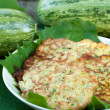 Pancakes with fresh zucchini on grape leaves - Stock Photo