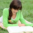 Girl reading a book lying on the grass — Stock Photo