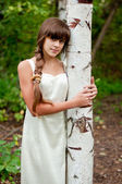 Russian girl in a white dress in a birch forest — Stock Photo
