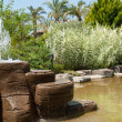 Landscaping - a stone fountain and pond - Stock Photo