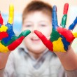 Boy with hands soiled in a paint — Stock Photo