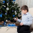 Boy with gifts near a Christmas tree — Stock Photo #16331815