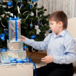 Boy with gifts near a Christmas tree — Stock Photo