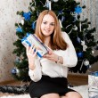 A young woman with gifts near a Christmas tree — Stock Photo