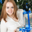 A young woman with gifts near a Christmas tree — Stock Photo #16339797