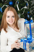 A young woman with gifts near a Christmas tree — Stok fotoğraf