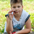 Boy with cherries in the garden — Stock Photo #17190215