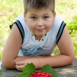 Boy with cherries in the garden — Stock Photo #17190219