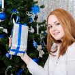 A young woman with gifts near a Christmas tree — Stock Photo #17673389
