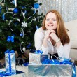 A young woman with gifts near a Christmas tree — Stock Photo #17673391