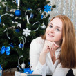 A young woman with gifts near a Christmas tree — Stock Photo #17673393