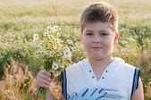 一个男孩用一束雏菊字段中 — 图库照片