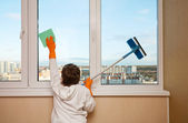 A boy washes a window — Stock Photo