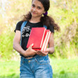 Stock Photo: Teen girl with books on nature