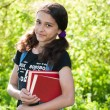 Teen girl with books on nature — Stock Photo #25522891
