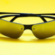 Mirrored sunglasses on yellow background — Stock Photo