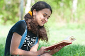 Teen girl reading a book on nature — Stock Photo