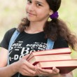 Teen girl with books on nature — Stock Photo