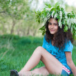 Teen girl with a wreath of cherry blossoms on her head — Stock Photo