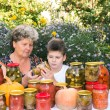 Grandmother with her grandson and home canned vegetables — Stock Photo